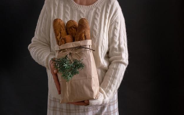 Mani della donna che tengono il sacchetto della spesa con pane per le vacanze di capodanno o natale Foto Premium