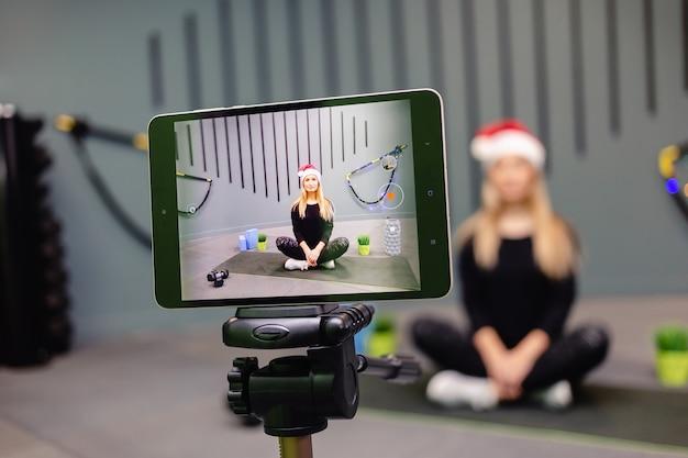 Donna in istruttore di fitness cappello da babbo natale registrazione video blog utilizzando la fotocamera su treppiede. Foto Premium