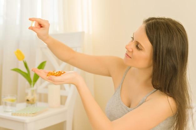La donna seduta mattina a letto prende vitamine, olio di pesce omega-3 vitamina e Foto Premium