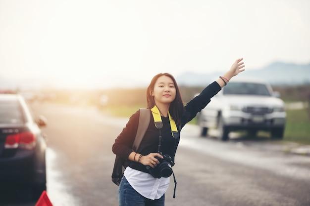 Donna in piedi con le braccia alzate sul ciglio della strada. dopo un guasto alla macchina Foto Premium