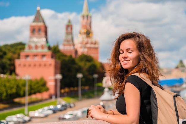 Una donna si trova su un ponte con uno spazio sul cremlino di mosca, l'attrazione principale della russia Foto Premium