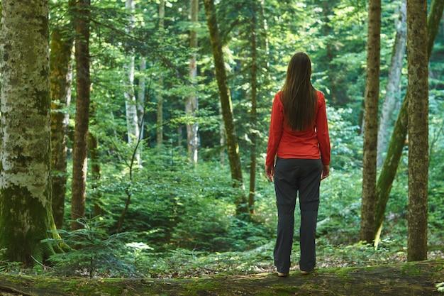 La donna sta in una foresta confidente senza una strada. perso nei boschi. Foto Premium