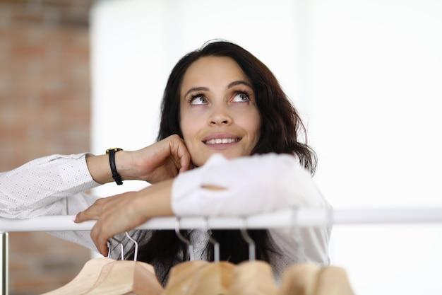 La donna sta con i gomiti sulla gruccia e alza lo sguardo sognante Foto Premium