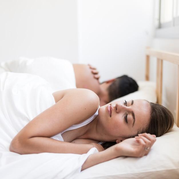 Donna che soffre di insonnia sdraiata sul letto vicino a suo marito Foto Premium