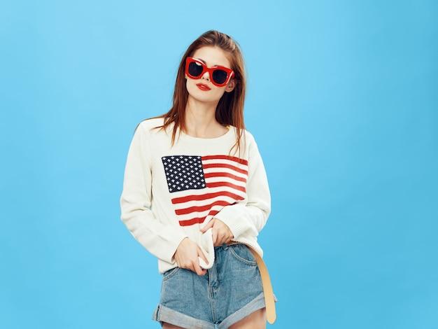 Donna in maglione con l'immagine della bandiera dell'america. giorno della bandiera americana e paese indipendente Foto Premium