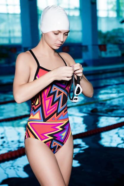 Il nuotatore della donna in una cuffia da nuoto veste gli occhiali e pronto a nuotare Foto Premium