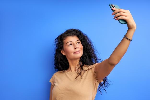 La donna prende selfie sul telefono, guardando lo smartphone. isolato sulla parete blu Foto Premium