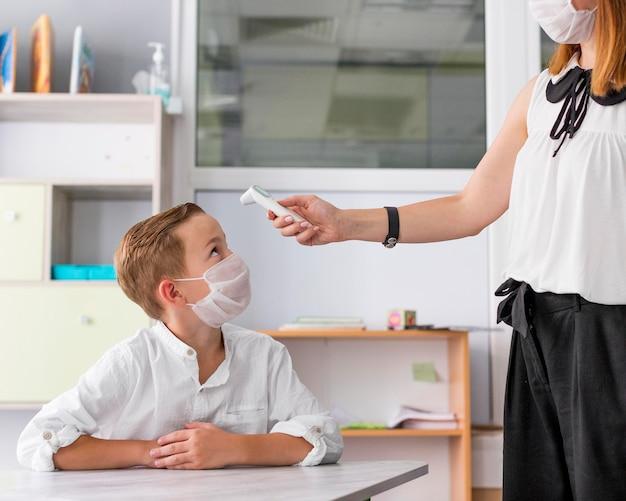 Donna che misura la temperatura di un bambino in classe Foto Premium