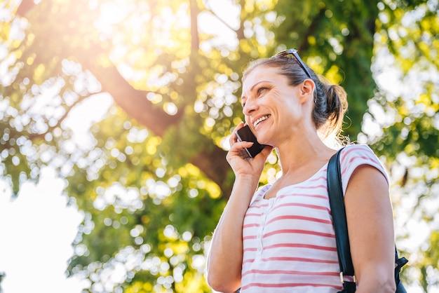 Donna che parla sul telefono cellulare nel parco Foto Premium