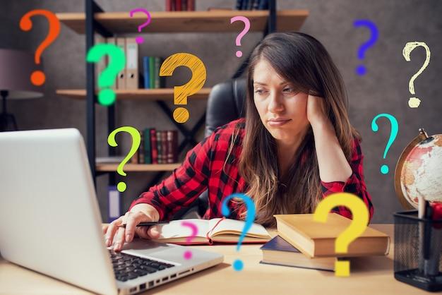 La telelavoratrice lavora a casa con un laptop con molte domande. Foto Premium
