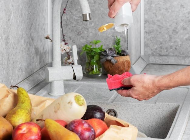 Donna che lava accuratamente frutta e verdura dopo lo shopping presso il negozio. il concetto di igiene personale in dettaglio, la lotta contro virus e batteri. primo piano, assistenza sanitaria Foto Premium
