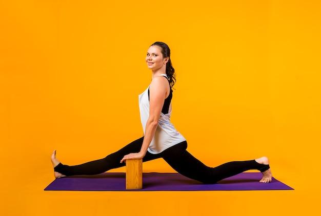 Una donna in tuta esegue esercizi di yoga con mattoni su una stuoia viola su una parete arancione Foto Premium