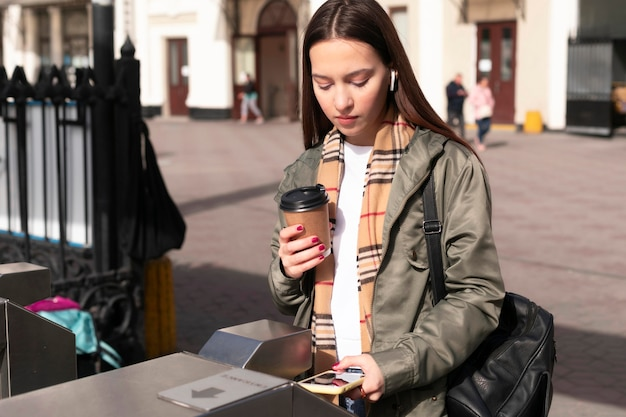 Donna ai tornelli che tengono caffè Foto Premium