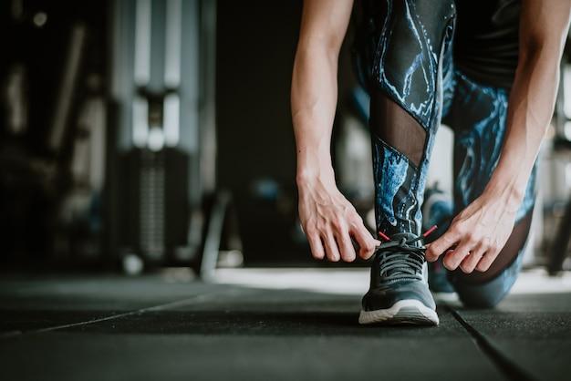 Donna che lega i suoi lacci delle scarpe prima dell'esercizio Foto Premium