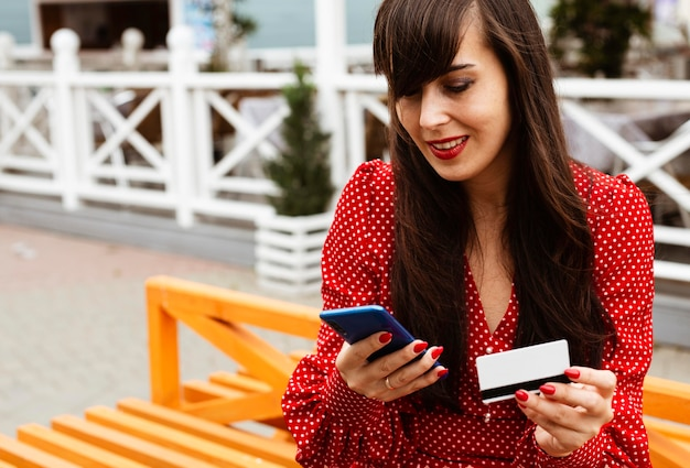 Donna che utilizza smartphone e carta di credito per acquistare le vendite online Foto Premium