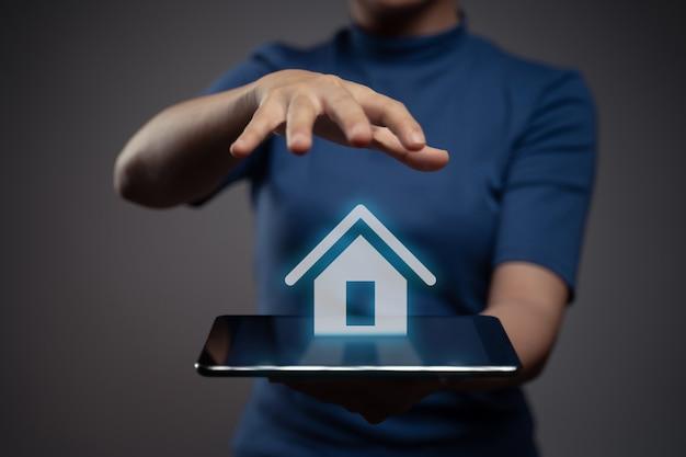 Donna che utilizza tablet che mostra con effetto ologramma icona home Foto Premium