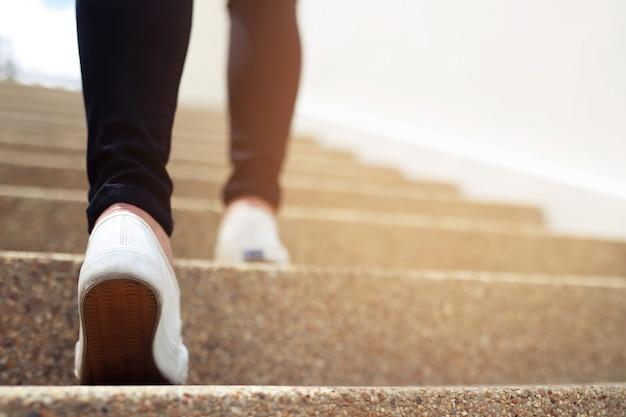 Donna che cammina su per le scale in un edificio per uffici Foto Premium