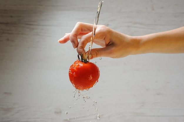 La donna lava un pomodoro Foto Premium