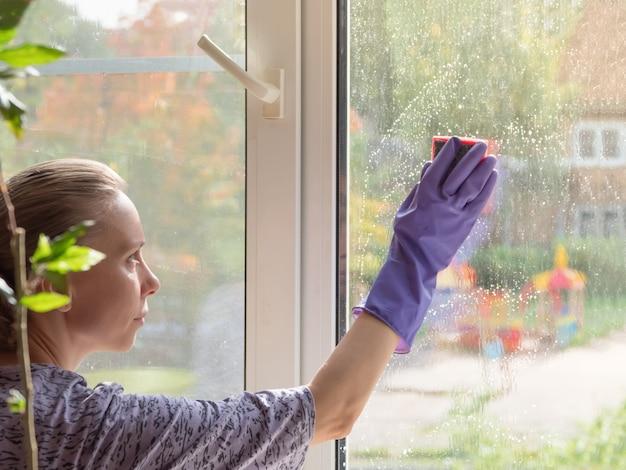 La donna lava la finestra con una spugna. pulizie di casa. lavaggio di detersivi per vetri sporchi in inverno. Foto Premium