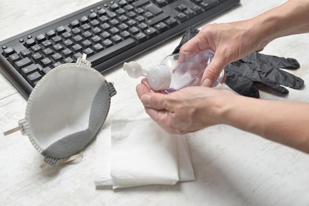 Donna che si lava le mani con gel idroalcolico all'ufficio Foto Premium