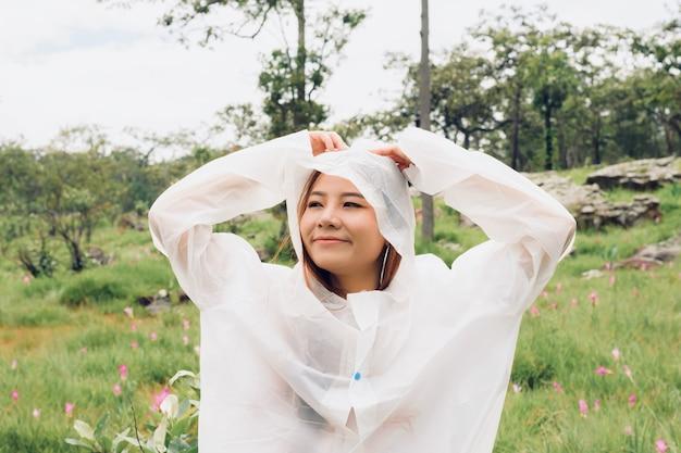 La donna indossa un impermeabile stand nella foresta pluviale Foto Premium