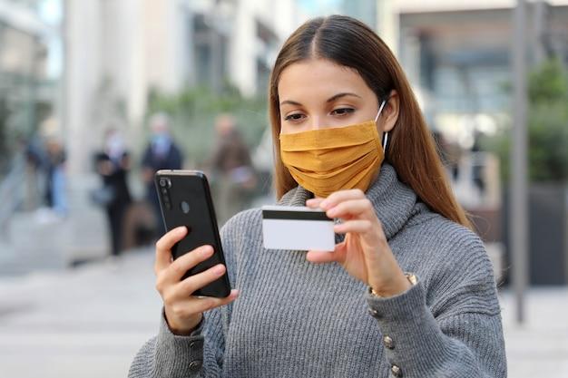 La donna che indossa la maschera protettiva si rilassa ed effettua il pagamento tramite carta di credito e telefono Foto Premium