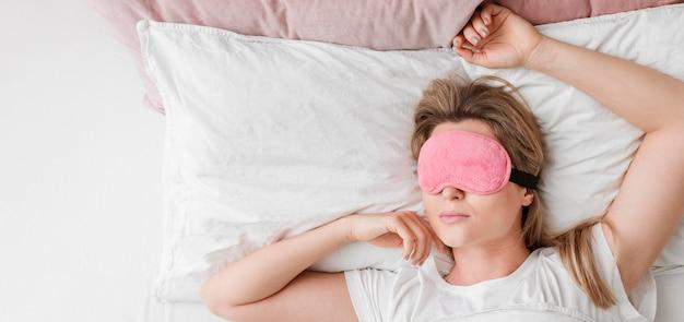 Donna che indossa una maschera per dormire sulla sua distesa piatta occhi Foto Premium