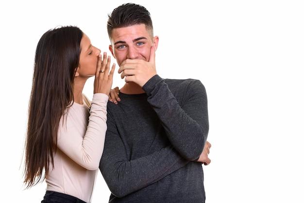 Donna che bisbiglia segreto all'uomo mentre l'uomo sembra sorpreso Foto Premium
