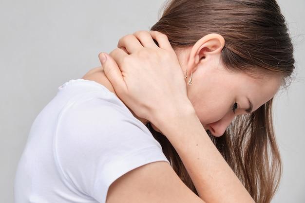 Una donna con una camicia bianca le massaggia il collo. dolore da osteocondrosi nella colonna cervicale. Foto Premium