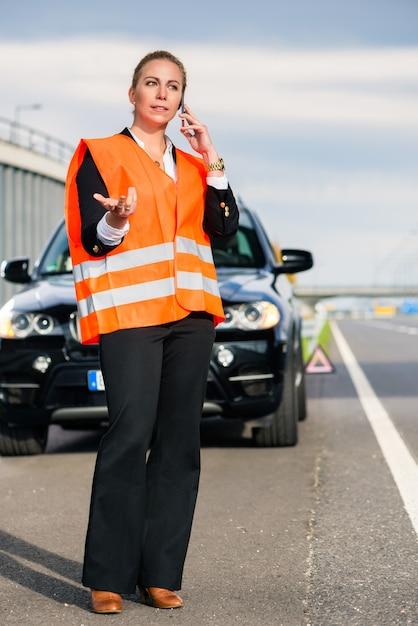 Donna con la ripartizione dell'automobile che chiama la società di rimorchio Foto Premium