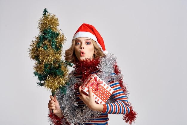 Donna con un albero di natale e regali cap sfondo chiaro modello capodanno. foto di alta qualità Foto Premium