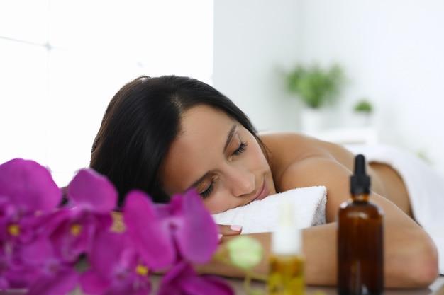 La donna con gli occhi chiusi si trova sul lettino da massaggio nel salone della stazione termale. rilassamento e relax dopo un concetto di giornata lavorativa Foto Premium