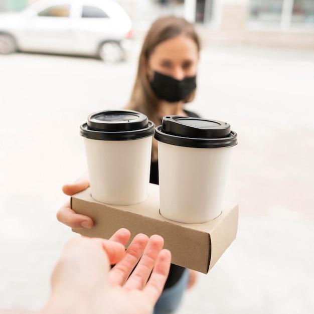 La donna con la maschera che riceve riceve porta via i caffè Foto Premium