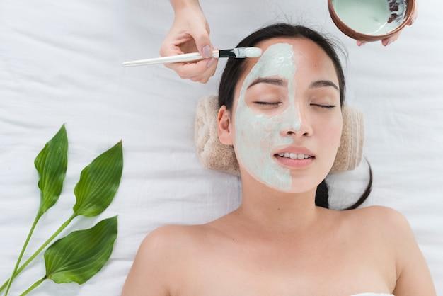 Donna con una maschera facciale in una spa Foto Premium