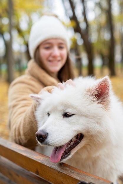 Donna con il suo cane in autunno in un parco. la donna lo sta accarezzando sulla panchina, sorridendo. Foto Premium
