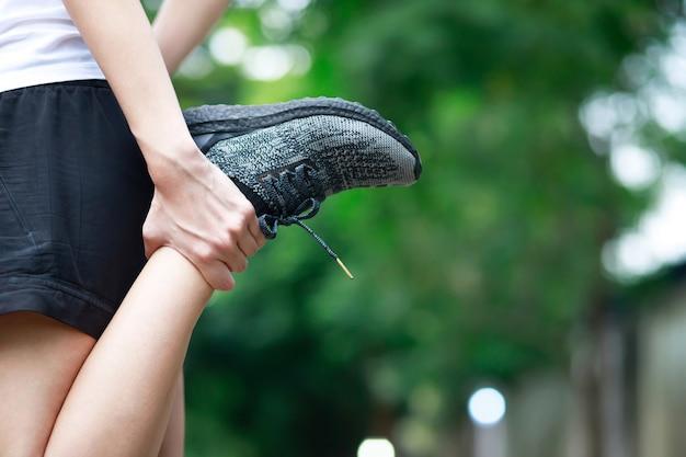 Una donna con un dolore alla gamba nel parco Foto Premium