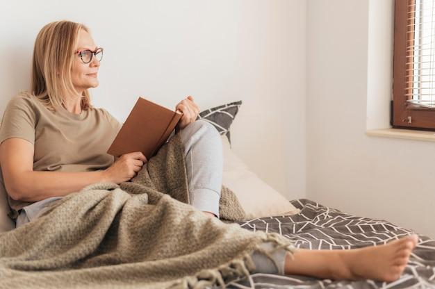 Donna con mascherina medica a casa leggendo il libro in quarantena Foto Premium