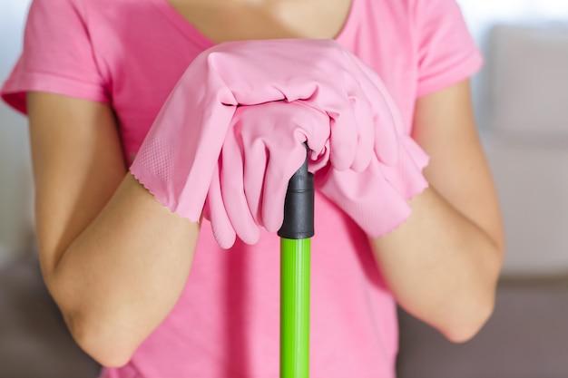 Donna con guanti protettivi utilizzando una scopa per pulire il pavimento Foto Premium