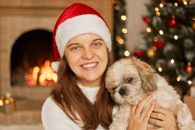 Donna con il sorriso a trentadue denti che abbraccia il suo piccolo cane barboncino, indossa un cappello natalizio e un maglione bianco, essendo nella stanza decorata con luci, albero di natale, in posa vicino al camino. Foto Premium