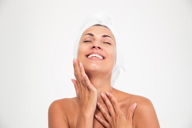 Donna con un asciugamano sulla testa che tocca il suo fac Foto Premium