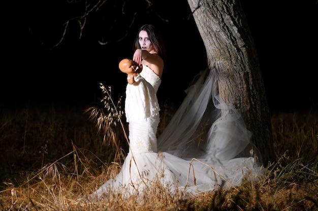 Donna con la faccia bianca e il vestito che tiene una bambola Foto Premium