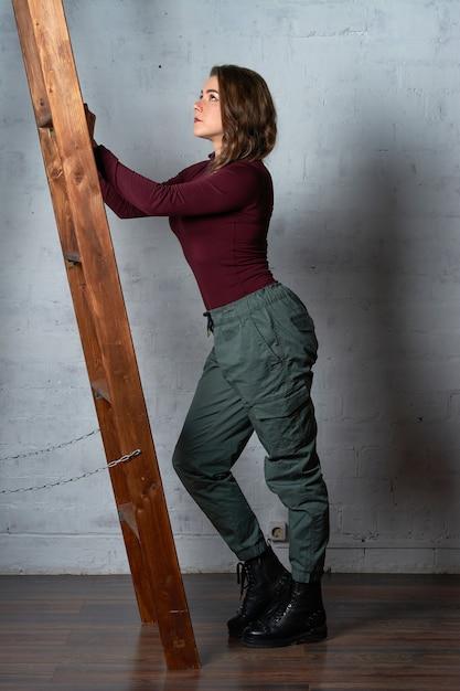Una donna con una scala di legno sta contro un muro di mattoni bianchi Foto Premium