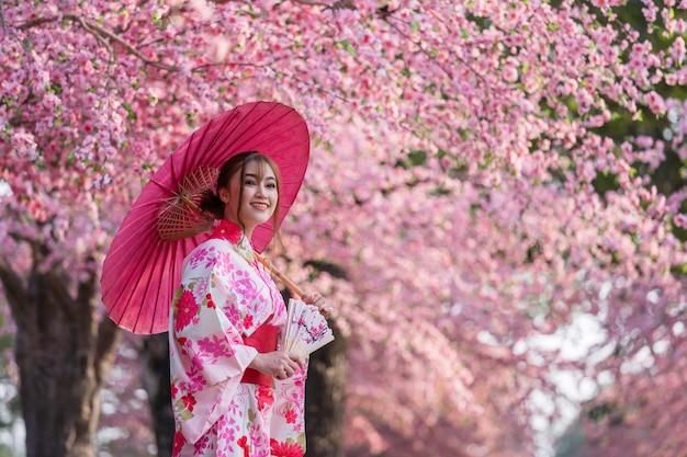 Donna in yukata (abito kimono) con ombrello e ventaglio pieghevole e guardando sakura fiore o fiore di ciliegio in fiore nel giardino Foto Premium