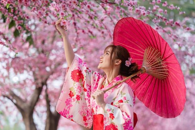 Donna in yukata (abito kimono) tenendo l'ombrello e guardando sakura fiore o fiore di ciliegio in fiore nel giardino Foto Premium