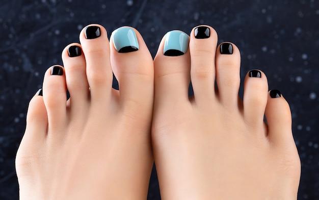 Piedi di womans su sfondo scuro. bellissimo design per unghie blu e nero primavera estate. manicure, concetto di salone di bellezza pedicure. Foto Premium