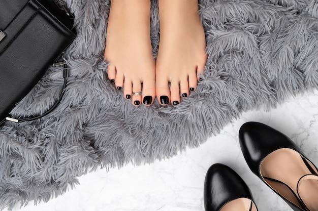 Piedi di donna con accessori su sfondo grigio peloso. bellissimo design classico delle unghie nere. manicure, concetto di salone di bellezza pedicure. Foto Premium