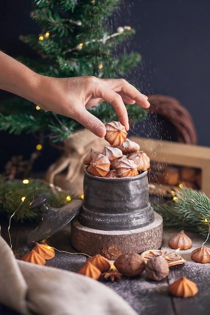 La mano della donna tiene il biscotto picci - biscotti di pasta frolla di natale in vaso vintage su sfondo di rami di abete. Foto Premium