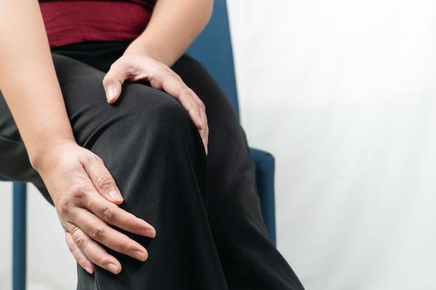 Le donne doloranti al ginocchio, le donne toccano il dolore al ginocchio a casa Foto Premium