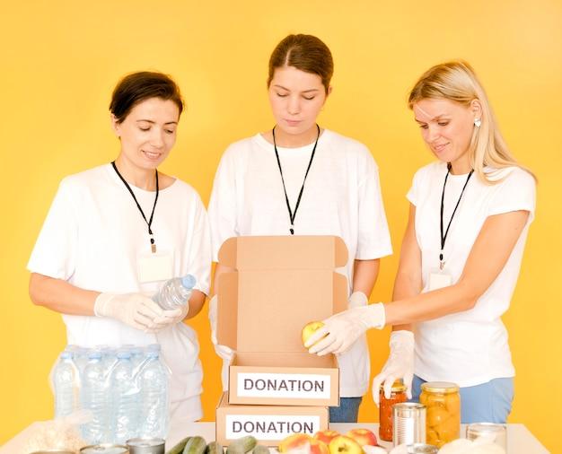 Donne che preparano scatole da donare per la giornata del cibo Foto Premium