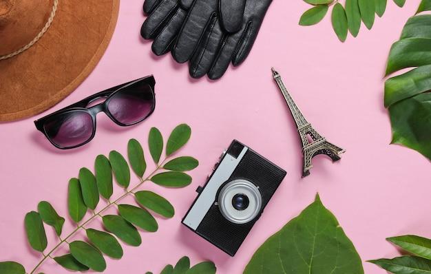 Accessori da donna, fotocamera retrò, statuetta della torre eiffel su sfondo rosa pastello con foglie verdi. vista dall'alto Foto Premium